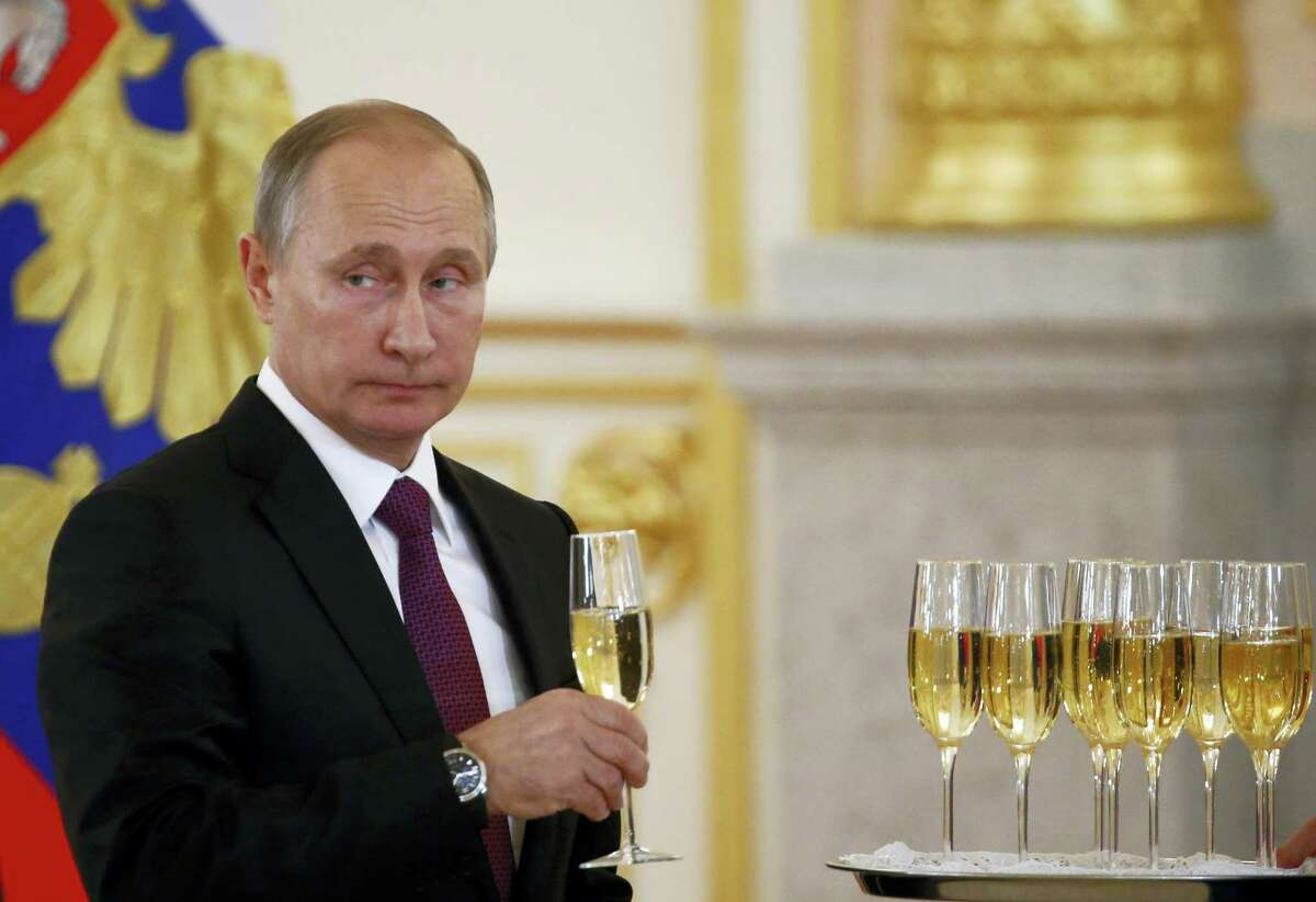 Russian President Vladimir Putin holds a glass during a ceremony of receiving diplomatic credentials from foreign ambassadors in the Kremlin in Moscow, Russia on Wednesday, Nov. 9, 2016. Putin says that Moscow is ready to try to restore good relations with the United States in the wake of the election of Donald Trump.