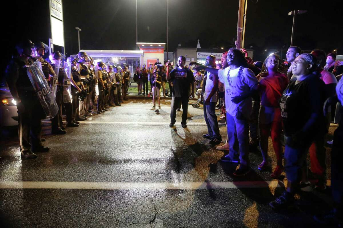 Protesters yell as police form a line across West Florissant Ave. on Aug. 9, 2015, in Ferguson, Mo., before shots were fired near the protest. The one-year anniversary of Michael Brown's death in Ferguson began with a march in his honor and ended with a protest that was interrupted by gunfire.