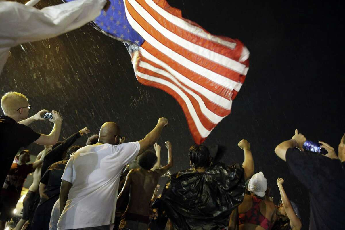 Protesters march in the rain on Aug. 9, 2015, in Ferguson, Mo. Sunday marks one year since Michael Brown was shot and killed by Ferguson police officer Darren Wilson.