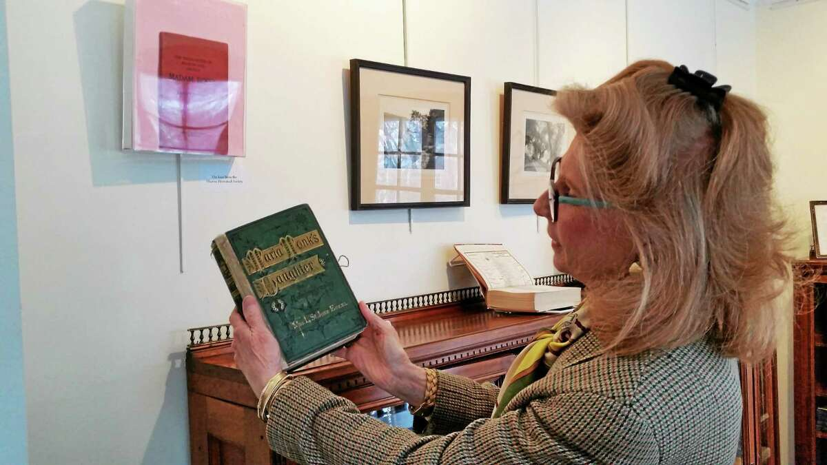 """Curator and library trustee Arete Warren shows a book that is part of the """"Mapping Sharon"""" exhibit running through May 3 at The Hotchkiss Library in Sharon."""