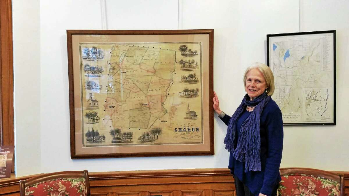 """Hotchkiss Library Executive Director Lorraine Kerr Faison is pictured at a historic map of Sharon, which is part of the """"Mapping Sharon"""" exhibit."""