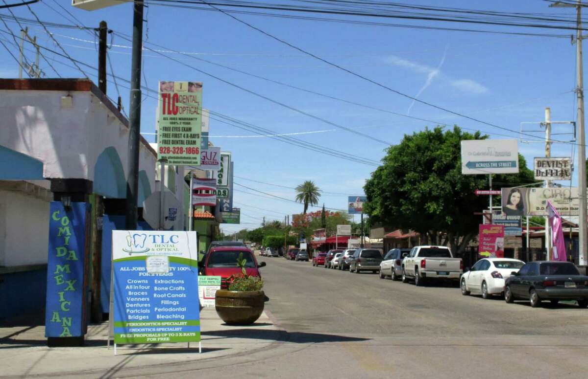 In this Thursday, April 30, 2015 photo, a street full of a dental offices is seen in Los Algodones, Mexico, which sits on the border with California. Thousands of Americans and Canadians travel to Los Algodones each year for affordable and reliable dental work from dentists who speak English and sometimes accept U.S. insurance. The trip, even counting the cost of traveling long distances, is often more affordable than getting dental care in the United States.