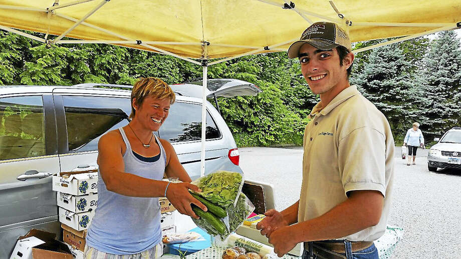 Emily Medonis of March Farm of Bethlehem sold green produce to Alex Maldonado of Laurel Ridge Farm of Litchfield during the Litchfield Hills Farm-Fresh Market at the Litchfield Center School parking lot at 125 West St. in Litchfield Saturday. Photo: N.F. Ambery — The Register Citizen