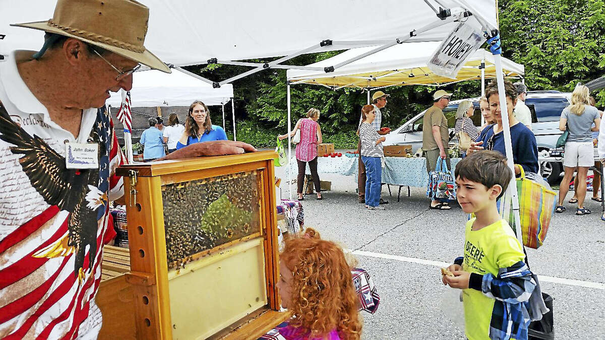 Beekeeper John Baker of Berry Ledges Apiary of Litchfield showed a beehive to Mimi Cotler, 4, and her brother, Dale Cotler, 6, at the Litchfield Hills Farm-Fresh Market at the Litchfield Center School parking lot at 125 West St. in Litchfield Saturday.
