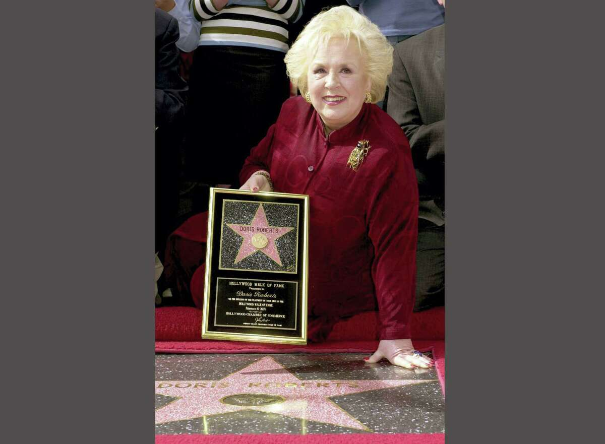 """FILE - In this Feb. 10, 2003 file photo, actress Doris Roberts poses by her star on the Hollywood Walk of Fame during a ceremony in Los Angeles. Family spokeswoman said that the """"Everybody Loves Raymond"""" actress Roberts has died at 90. (AP Photo/Nick Ut, File)"""