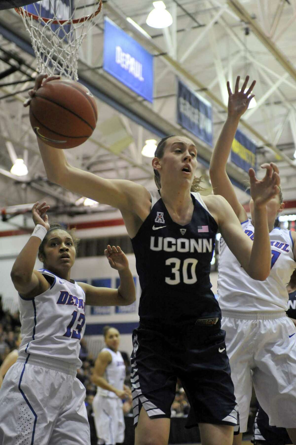Connecticut's Breanna Stewart (30), grabs the ball against DePaul's Chanise Jenkins (13), and Megan Podkowa (30), during the first half of an NCAA college basketball game Wednesday, Dec. 2, 2015, in Chicago. (AP Photo/Paul Beaty)