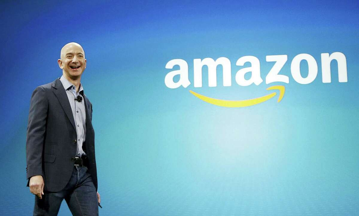 In this June 16, 2014 photo, Amazon CEO Jeff Bezos walks on stage for the launch of the new Amazon Fire Phone, in Seattle.