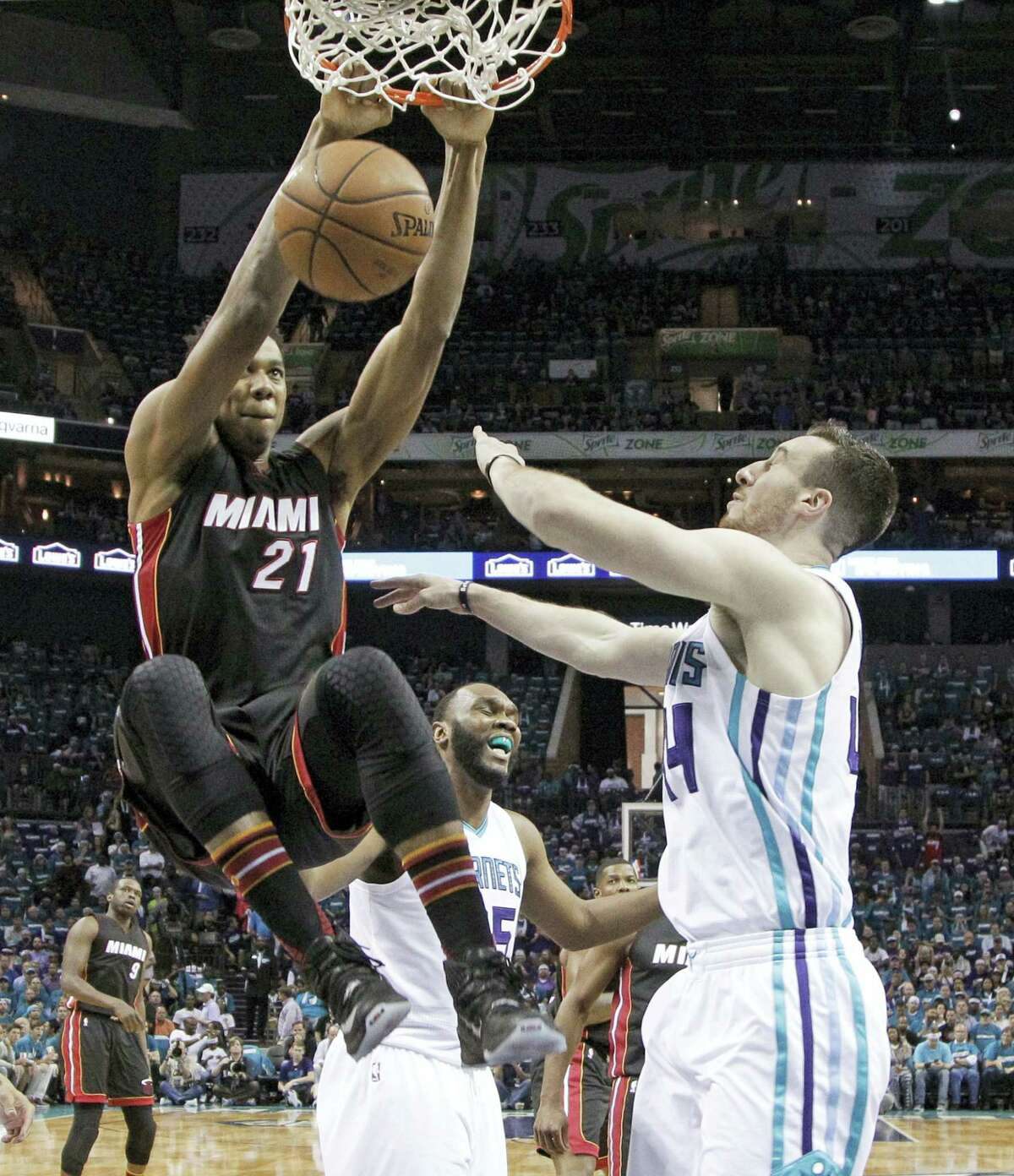 In this Monday, April 25, 2016 photo, Miami Heat's Hassan Whiteside (21) dunks over Charlotte Hornets' Frank Kaminsky (44) during the first half in Game 4 of an NBA basketball playoffs first-round series in Charlotte, N.C. Whiteside will be one of the most coveted targets when free agency begins FrIday, July 1, and there's no guarantee that the center whose career was resuscitated by the Miami Heat will be back with them next season.