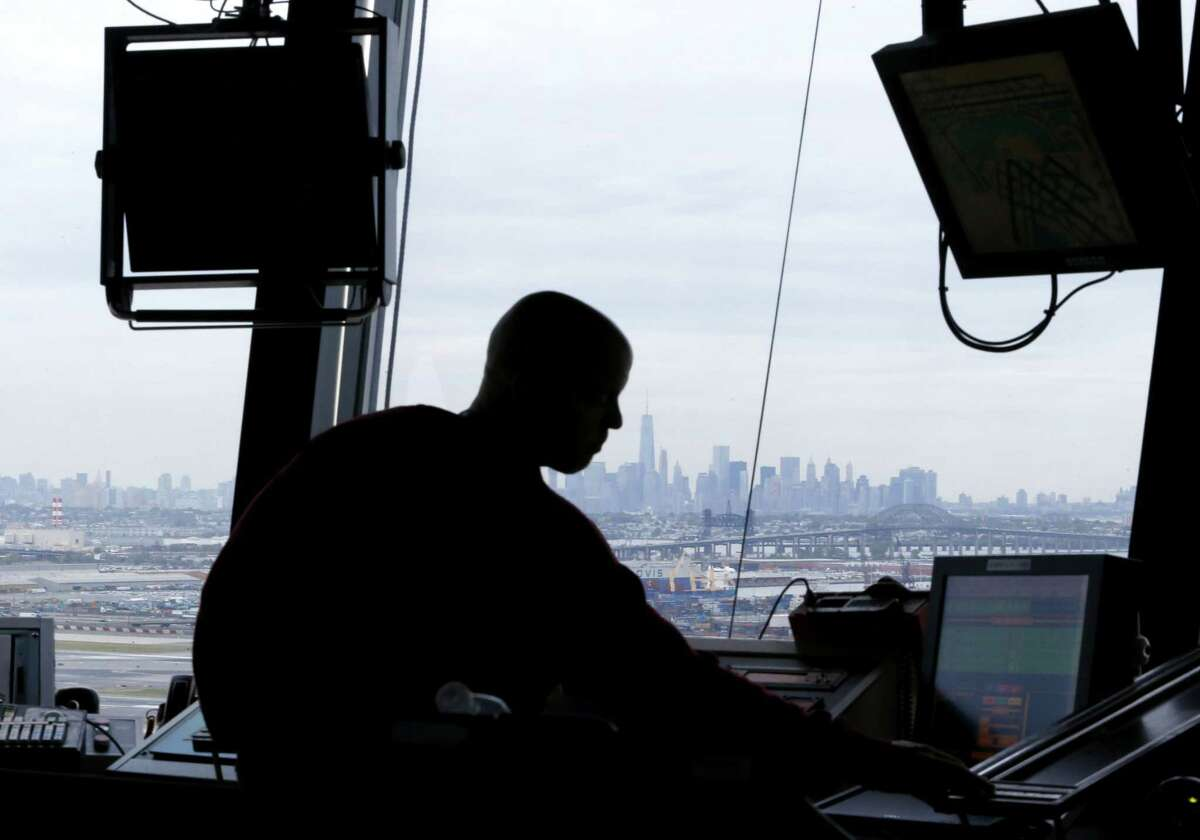 In this May 21, 2015 photo, an air traffic controller works in the tower at Newark Liberty International Airport in Newark, N.J.