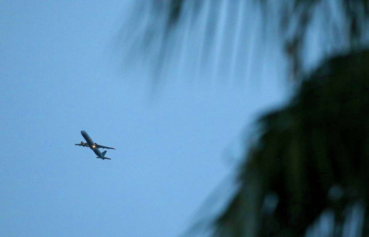 Framed by neighborhood palm trees, a passenger plane brings increased noise to residential neighborhoods like this one near Phoenix as new FAA flight routes out of Phoenix Sky Harbor International Airport are affecting dozens of neighborhoods with the new noise that residents previously did not have to be subjected to Friday, Feb. 20, 2015, in Laveen, Ariz.