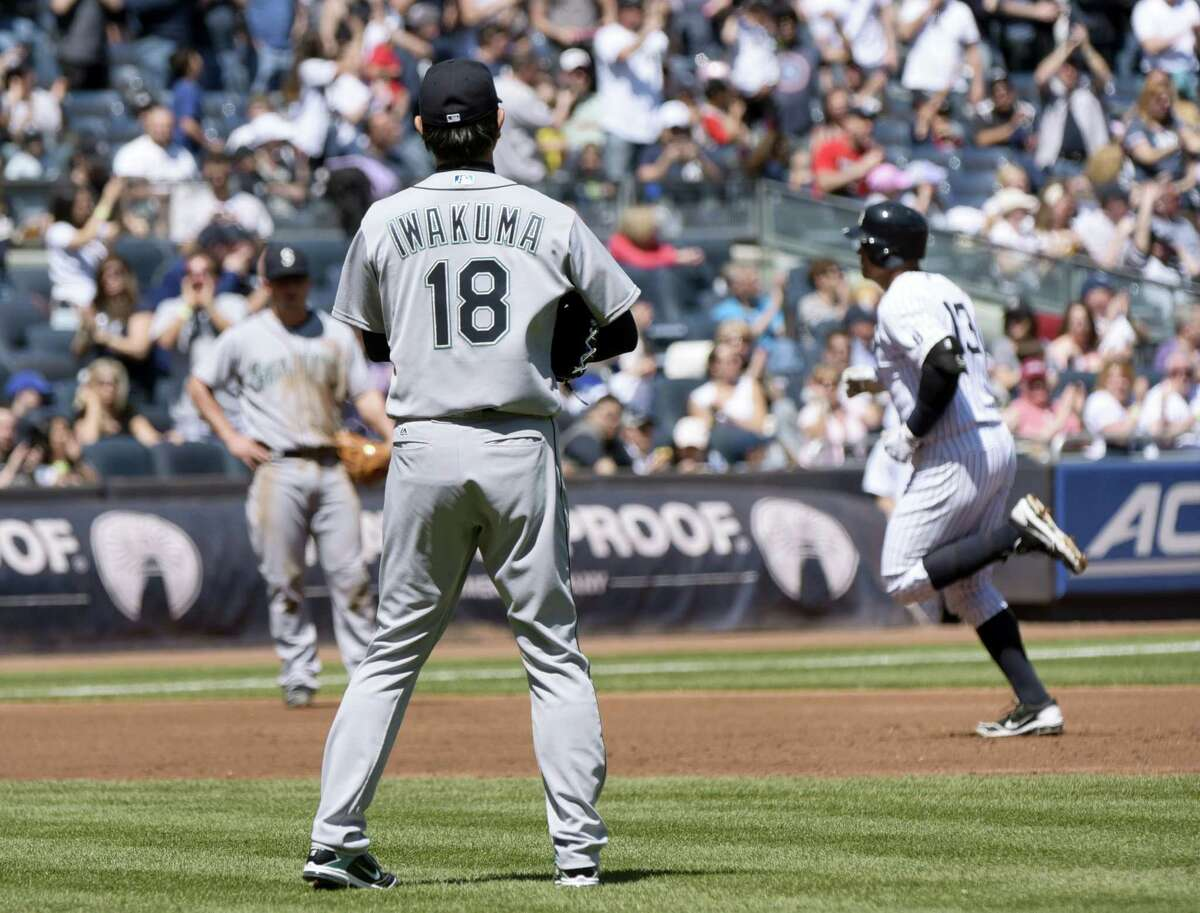 Mariners pitcher Hisashi Iwakuma watches as Alex Rodriguez rounds the bases after hitting a two-run home run in the second inning Sunday at Yankee Stadium.