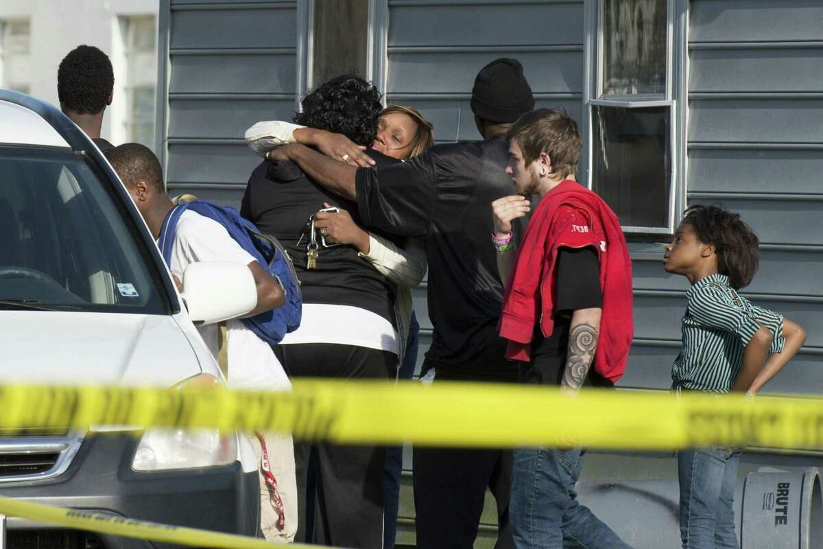 Onlookers gather outside of a house, where police say seven children and one adult have been found dead Monday in Princess Anne, Md.