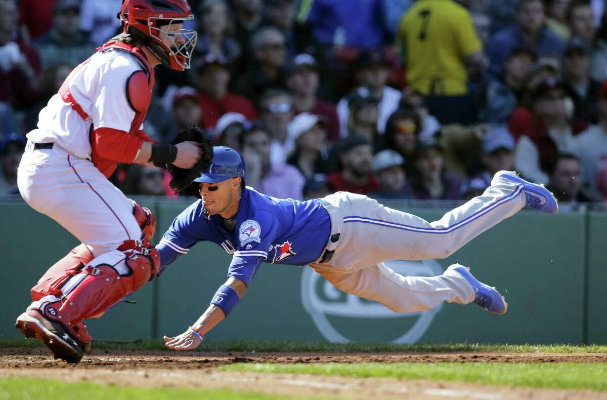 The Blue Jays' Ryan Goins, right, scores as Red Sox catcher Ryan Hanigan, left, waits for the ball in the seventh inning on Sunday.