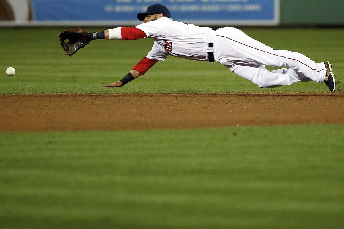 Boston Red Sox second baseman Dustin Pedroia can't make a diving grab on a Minnesota Twins base hit in the fourth inning of a spring training exhibition baseball game Friday, April 3, 2015, in Fort Myers, Fla. The Twins beat the Red Sox 5-2. (AP Photo/Naples Daily News, Corey Perrine)