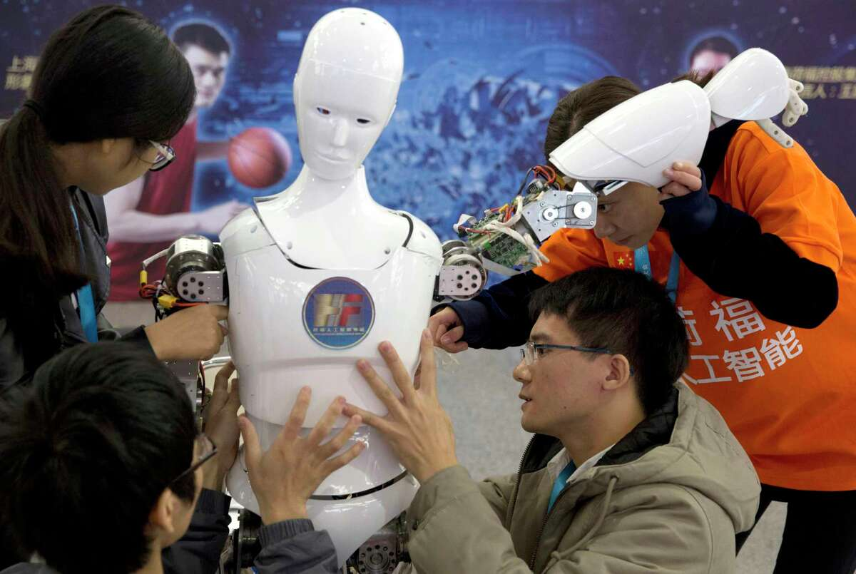 Chinese students work on the Ares, a humanoid bipedal robot designed by them with fundings from a Shanghai investment company, displayed during the World Robot Conference, which was held in Beijing earlier this summer.