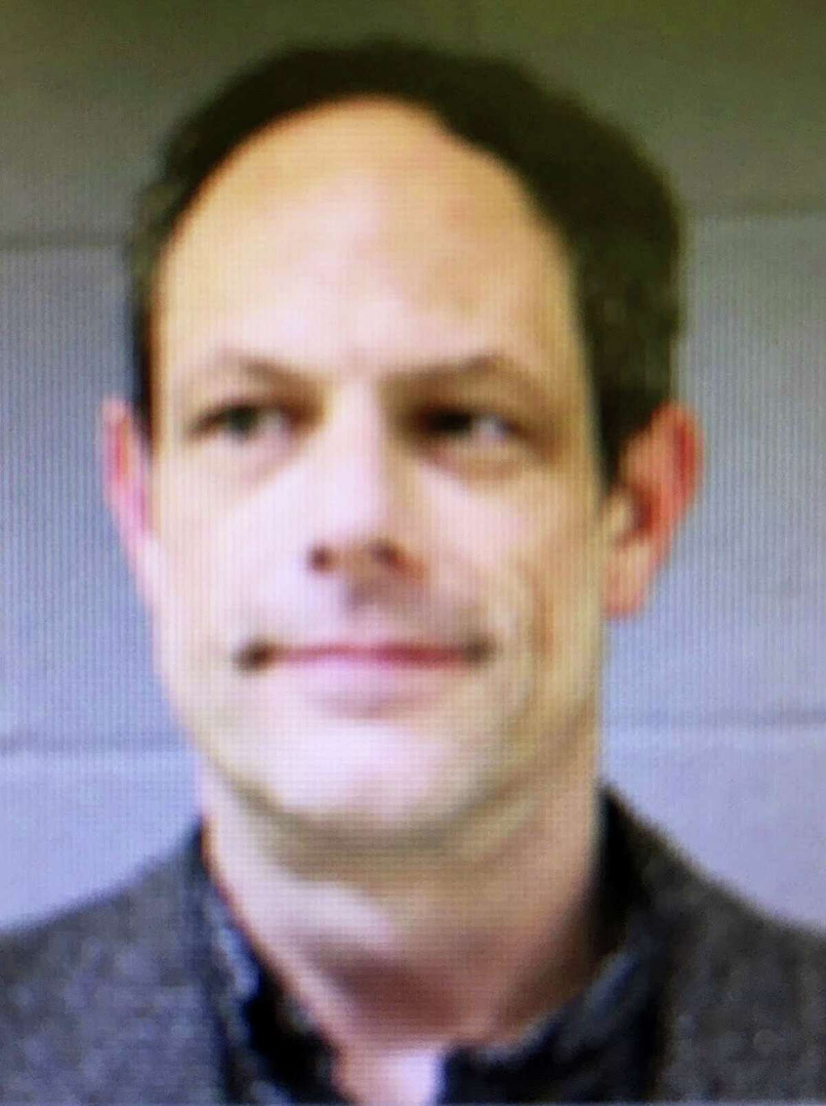 This booking photo released by the Newtown Police Department shows Jason Adams, arrested Wednesday, April 6, 2016, and charged with having a gun at the town's middle school. Adams, 46, a teacher at the school, was charged with possession of a weapon on school grounds, which is illegal in Connecticut.