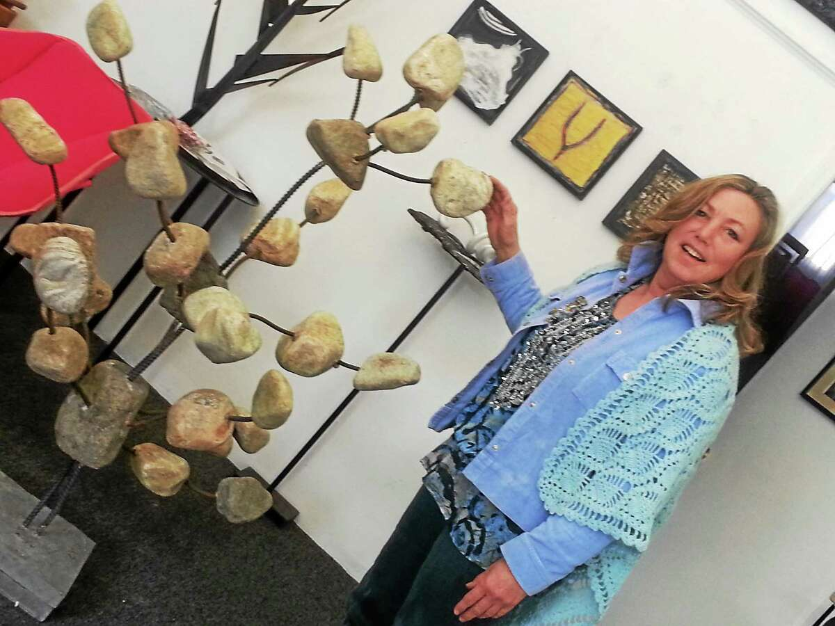 Karen Rossi shows off a work of art, intended to be a modern take on traditional stone cairns, placed in a neighborís gallery.
