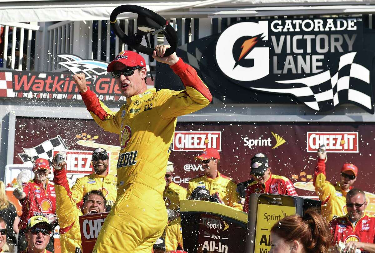 Joey Logano celebrates in Victory Lane after winning the NASCAR Sprint Cup race on Sunday at Watkins Glen International in Watkins Glen. N.Y.