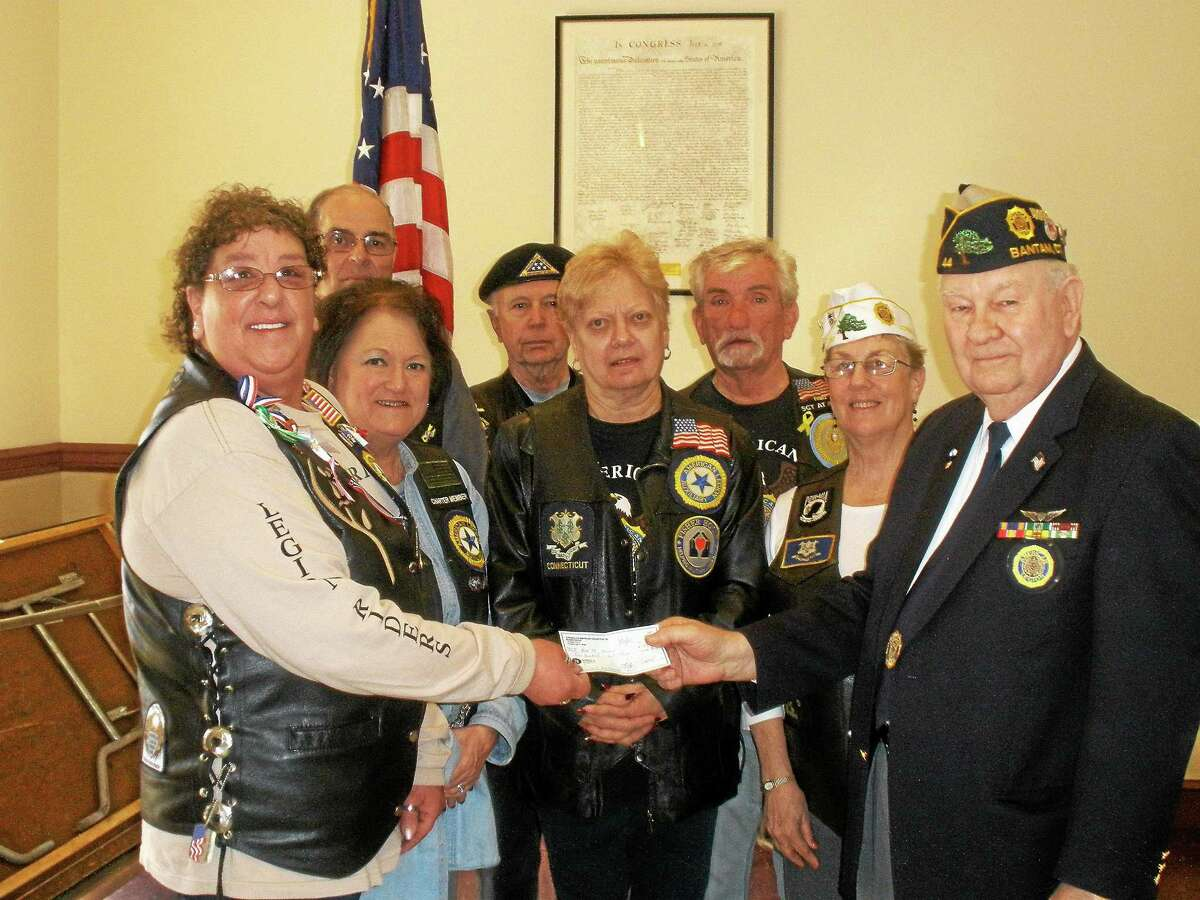Rose Bristol along with fellow American Legion Riders of Torrington presents John Lilley of Post 44 with a $100 dollar check for continued success.