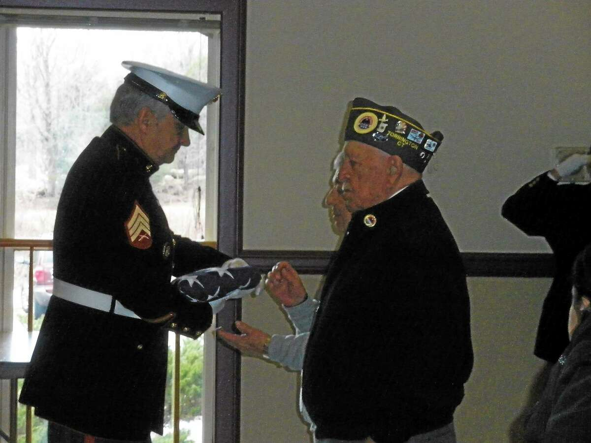 Roland Dupre presents the flag that will be flown at the All Wars Memorial until May 7.
