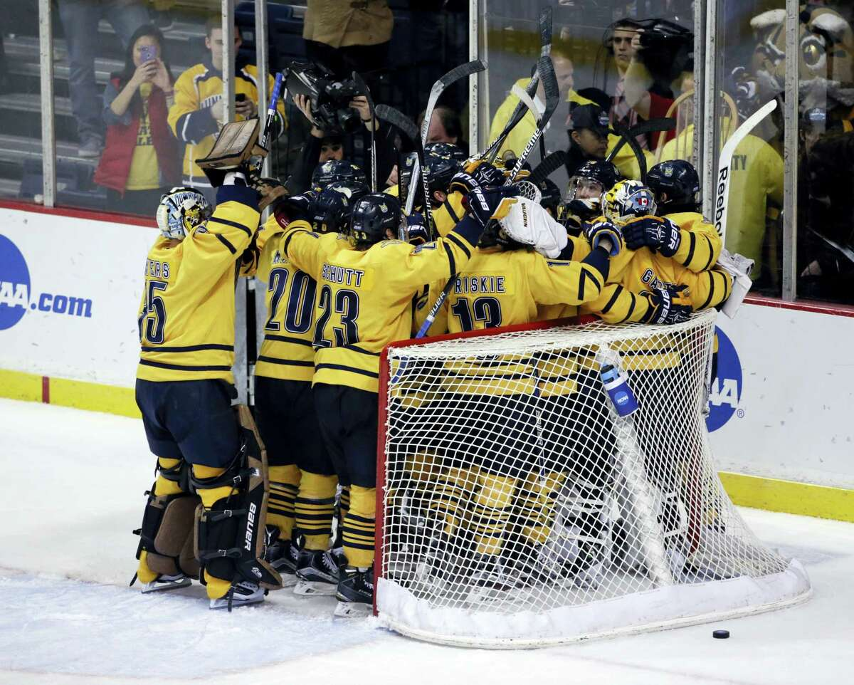 Members of the Quinnipiac hockey team celebrate their win over UMass Lowell in the NCAA East Regional championship.