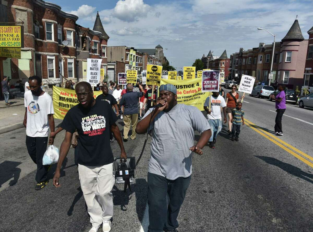 Andre Powell, left, an organizer with Baltimore People's Power Assembly, and Rev. C.D. Witherspoon, president of the Baltimore SCLC, lead a march on North Avenue in Baltimore on Aug. 8 2015, the eve of the anniversary of Michael Brown's death during a confrontation with a police officer.