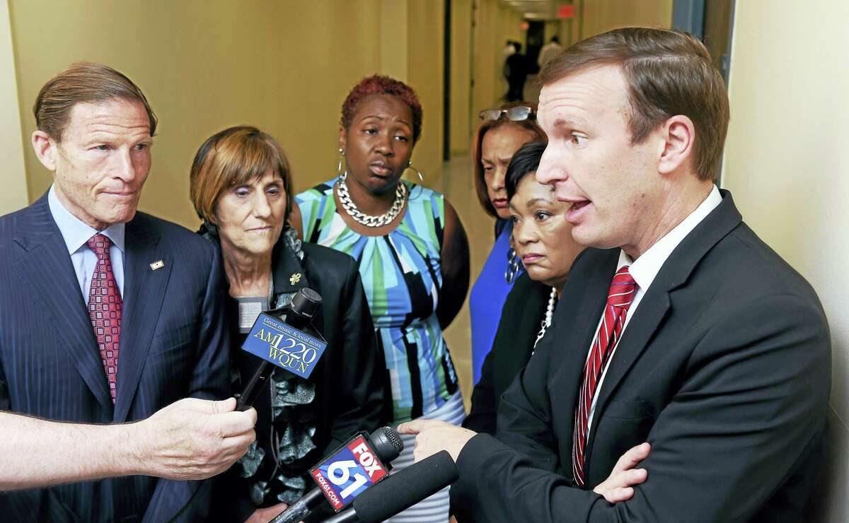U.S. Sen. Chris Murphy, right, makes a point about the stigma associated with opioid addiction and the lack of funding after a roundtable discussion about efforts to curb the opioid epidemic at the New Haven Police Department on Friday.