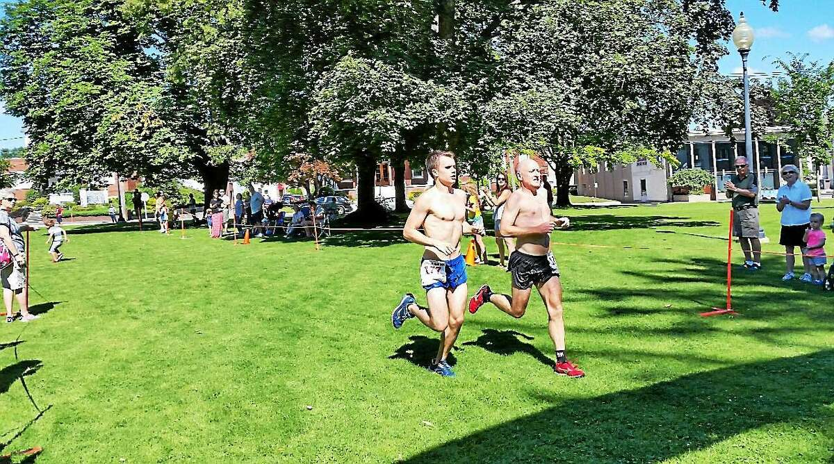 N.F. Ambery photo Chris Chisholm, 53, and his son Matthew Chisholm, 19, both of Farmington, tie for first place in the 44th annual five-mile Torrington Road Race.