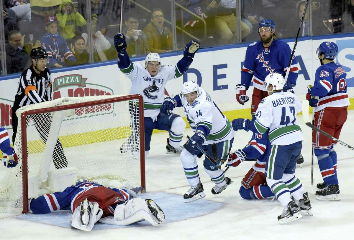 Vancouver Canucks' Alexandre Burrows (14) celebrates his goal against New York Rangers goaltender Henrik Lundqvist, left, with Bo Horvat (53) during the third period Tuesday at Madison Square Garden in New York. The Canucks won 5-3.
