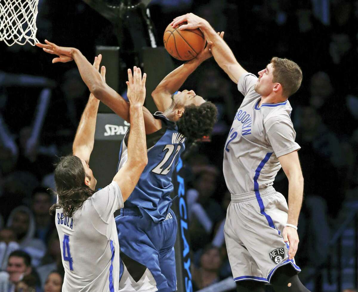 Brooklyn Nets guard Joe Harris (12) steals the ball from Minnesota Timberwolves forward Andrew Wiggins (22) as Brooklyn Nets' forward Luis Scola (4) defends Wiggins during the second half Tuesday in New York. The Nets defeated the Timberwolves 119-110.