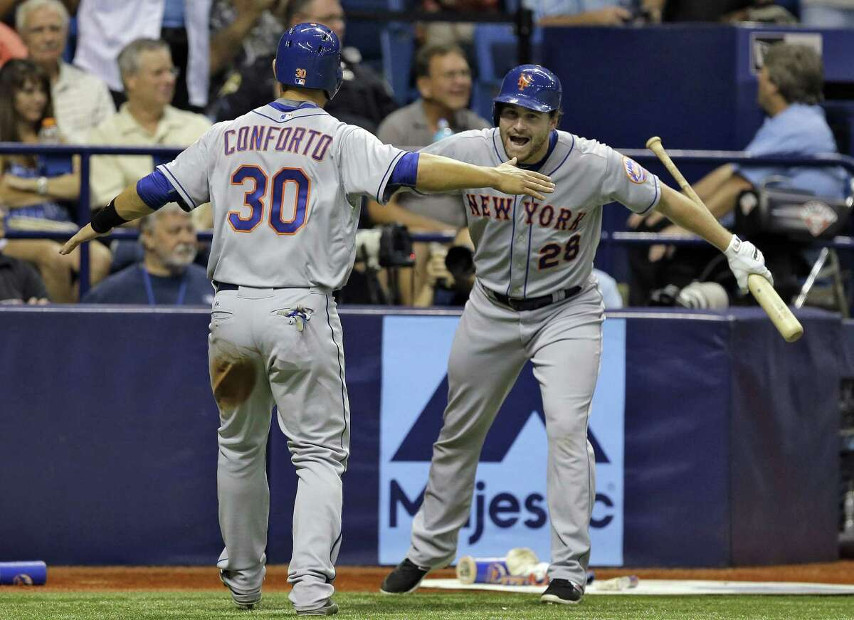 New York Mets rookie Michael Conforto celebrates with Daniel Murphy after scoring on an RBI single by Wilmer Flores in the ninth inning of Friday night's 4-3 win over the Tampa Bay Rays in St. Petersburg, Fla.