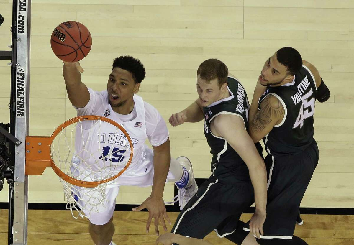 Duke's Jahlil Okafor (15) goes up for a shot against Michigan State's Colby Wollenman and Denzel Valentine (45) during the second half of the NCAA Final Four tournament college basketball semifinal game Saturday, April 4, 2015, in Indianapolis. (AP Photo/David J. Phillip)