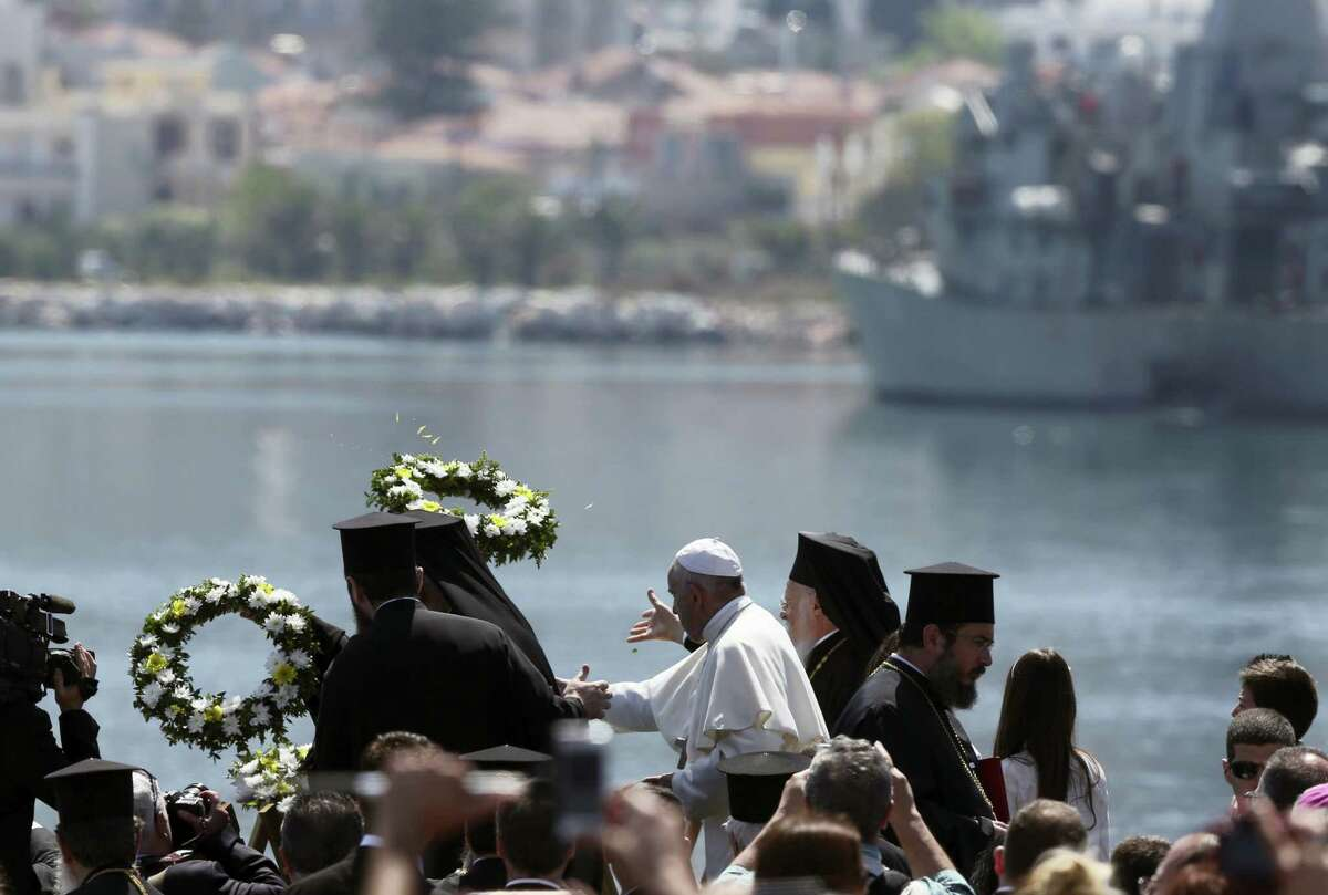 Pope Francis, center, flanked by Ecumenical Patriarch Bartholomew I, spiritual leader of the world's Orthodox Christians, left, and Archbishop of Athens and All Greece Ieronymos II, head of the Church of Greece, toss floral wreaths into the sea, on the Greek island of Lesbos, Saturday April 16, 2016. The heads of the Catholic and Orthodox churches have conducted a prayer ceremony for refugees at the port of Mytilene, the capital of the Greek island of Lesbos where hundreds of thousands of have passed through on perilous journeys from the Turkish coast toward Europe.