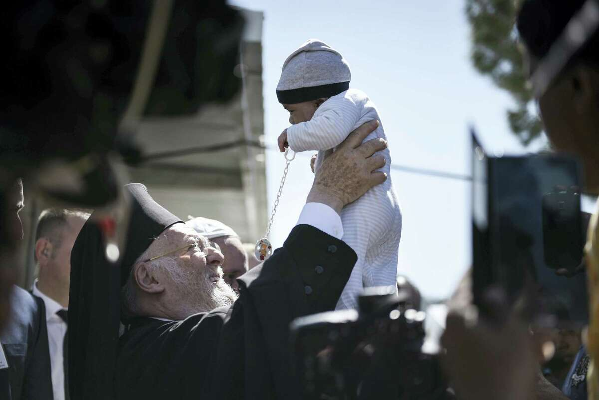 """In this photo released by Greek Prime Minister's office on Saturday, April 16, 2016, Ecumenical Patriarch Bartholomew I raises a baby during a visit along with Pope Francis and Orthodox Archbishop Ieronymos at the Moria refugee camp on the island of Lesbos, Greece. Pope Francis implored Europe on Saturday to respond to the migrant crisis on its shores """"in a way that is worthy of our common humanity,"""" during an emotional and provocative trip to Greece."""