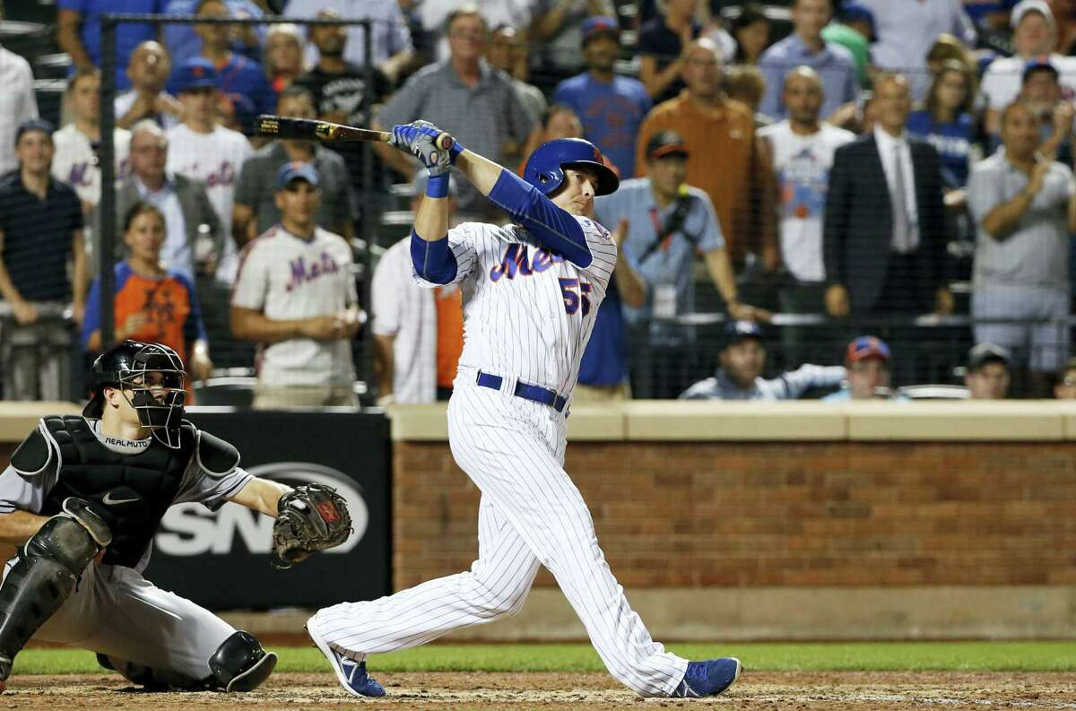 New York'S Kelly Johnson watches his three-run double in the eighth inning against the Miami Marlins Wednesday. The Mets won 5-2.