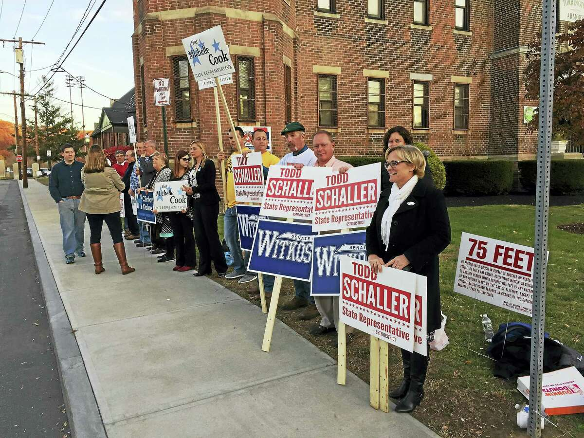 Ben Lambert — The Register Citizen Torrington Mayor Elinor Carbone, in the black coat, first from left, holds a sign for Republican candidates Kevin Witkos and Todd Schaller during Tuesday's election. Carbone joined other Republicans to rally support for candidates running for the state Senate and legislature.