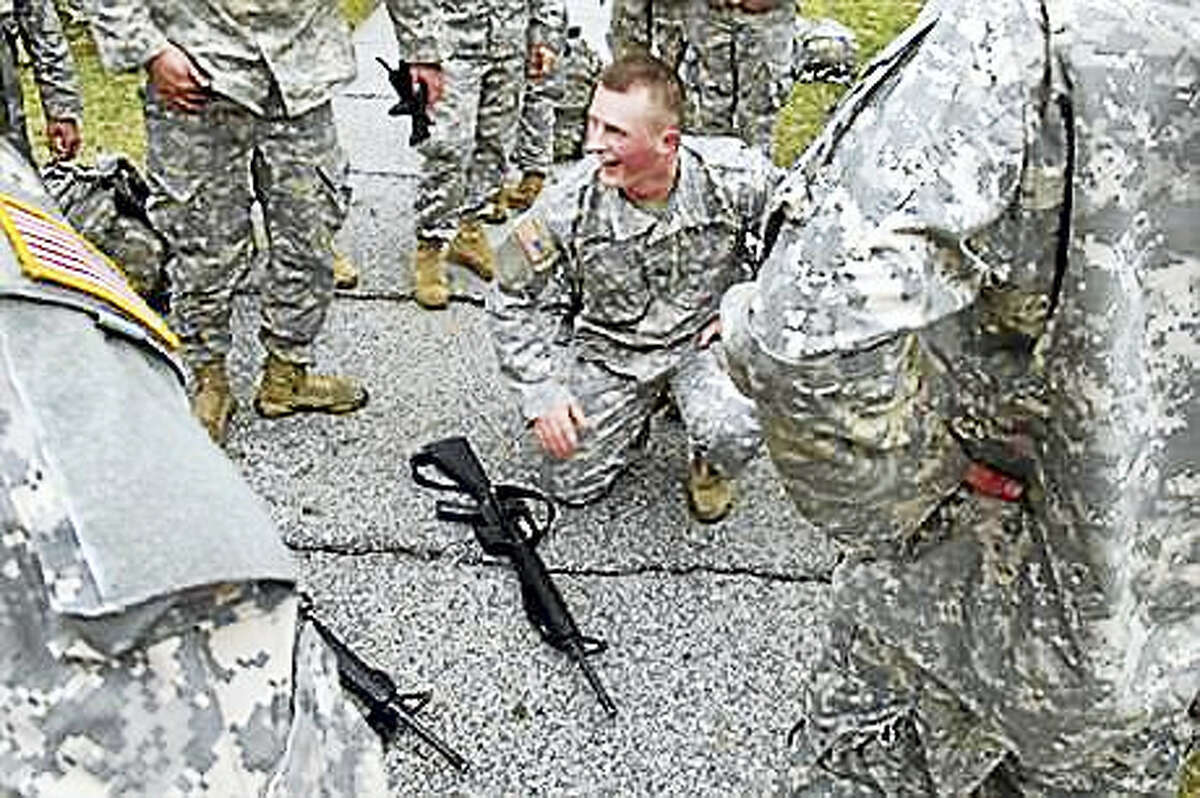 In this April 12, 2016, photo, ROTC cadet Jacob Jasewicz squats next to an unloaded rifle that was used as part of a training exercise at Norwich University in Northfield, Vt., The exercise is part of the training undergone by ROTC students at Norwich. On April 21 and 22, some of the nations top military officers will be at Norwich to commemorate the 100th anniversary of ROTC, which produces about 70 percent of the nations military officers.