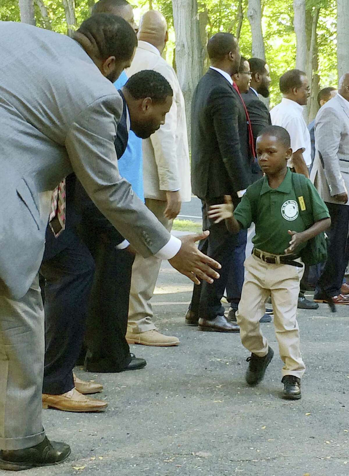 In this Aug. 30, 2016 photo, black professional men from the community greet students arriving for the first day of school at Martin Luther King Jr. Elementary School in Hartford, Conn. Similar welcome ceremonies have been staged for students from minority communities in cities around the country including Atlanta, Boston and Seattle.