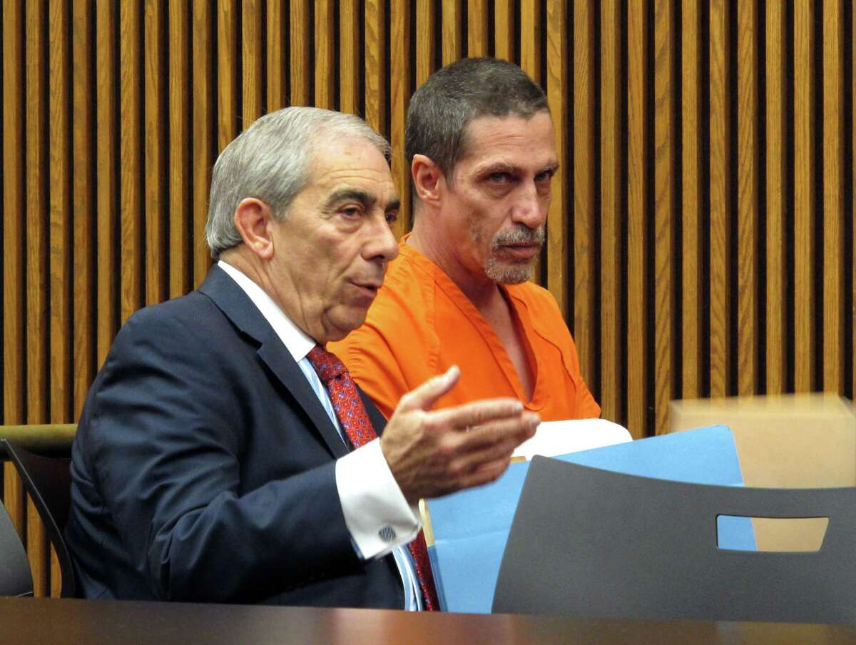 Bobby Hernandez, right, listens to defense attorney Ralph DeFranco in Cuyahoga County Common Pleas Court before pleading not guilty to kidnapping and other charges on Tuesday, Dec. 1, 2015, in Cleveland. Authorities allege Hernandez took his 5-year-old son from an Alabama home in 2002 and created a life for them in Ohio under new identities, a ruse discovered through discrepancies with the boy's Social Security number as he began the college application process.