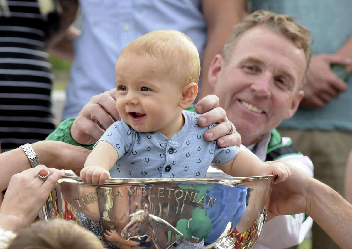 Trainer Jimmy Takter holds his grandson, Austin, in the Hambletonian Cup after Pinkman won the Hambletonian harness horse race Saturday in East Rutherford, N.J.
