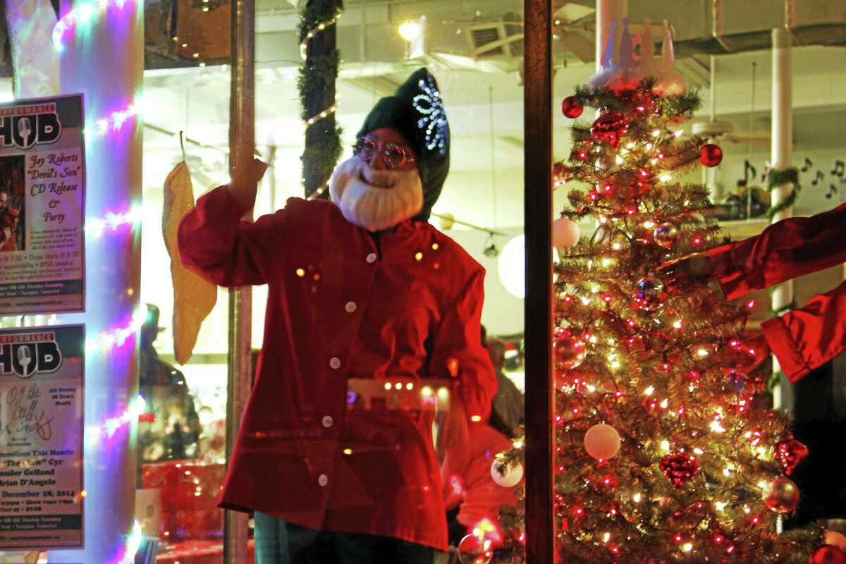 Gina Pirla, 16, greets people inside one of the windows of Performance HUB as an elf on during the Christmas Village Toy Shower in Torrington.