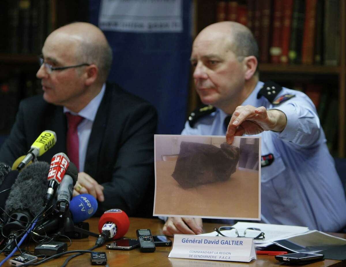 General David Galtier, flanked by Marseille prosecutor Brice Robin, left, displays a picture showing the second black box from the Germanwings plane that crashed in the French Alps last week, during a press conference Thursday in Marseille, southern France.