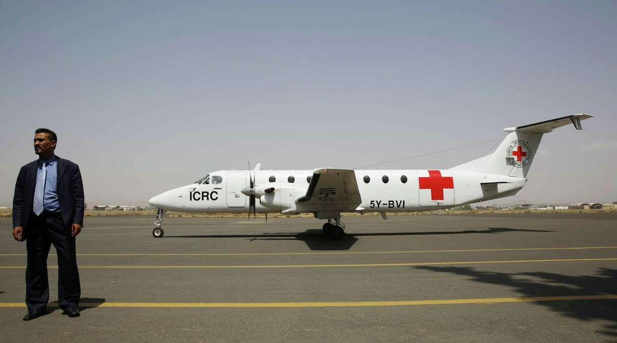 A Yemeni airport security official stands by a plane of the International Committee of the Red Cross on the tarmac of the international airport in Sanaa, Yemen, Saturday, Aug. 8, 2015.