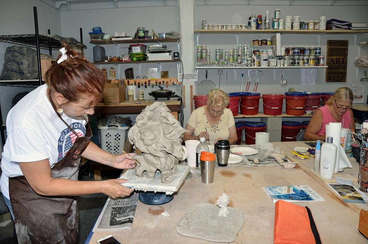 Pat Jasinnas, left, owner of the Earth to Fire pottery studio and retail store in Southport, N.C., works on her lion while two of her Monday gang work on their projects.