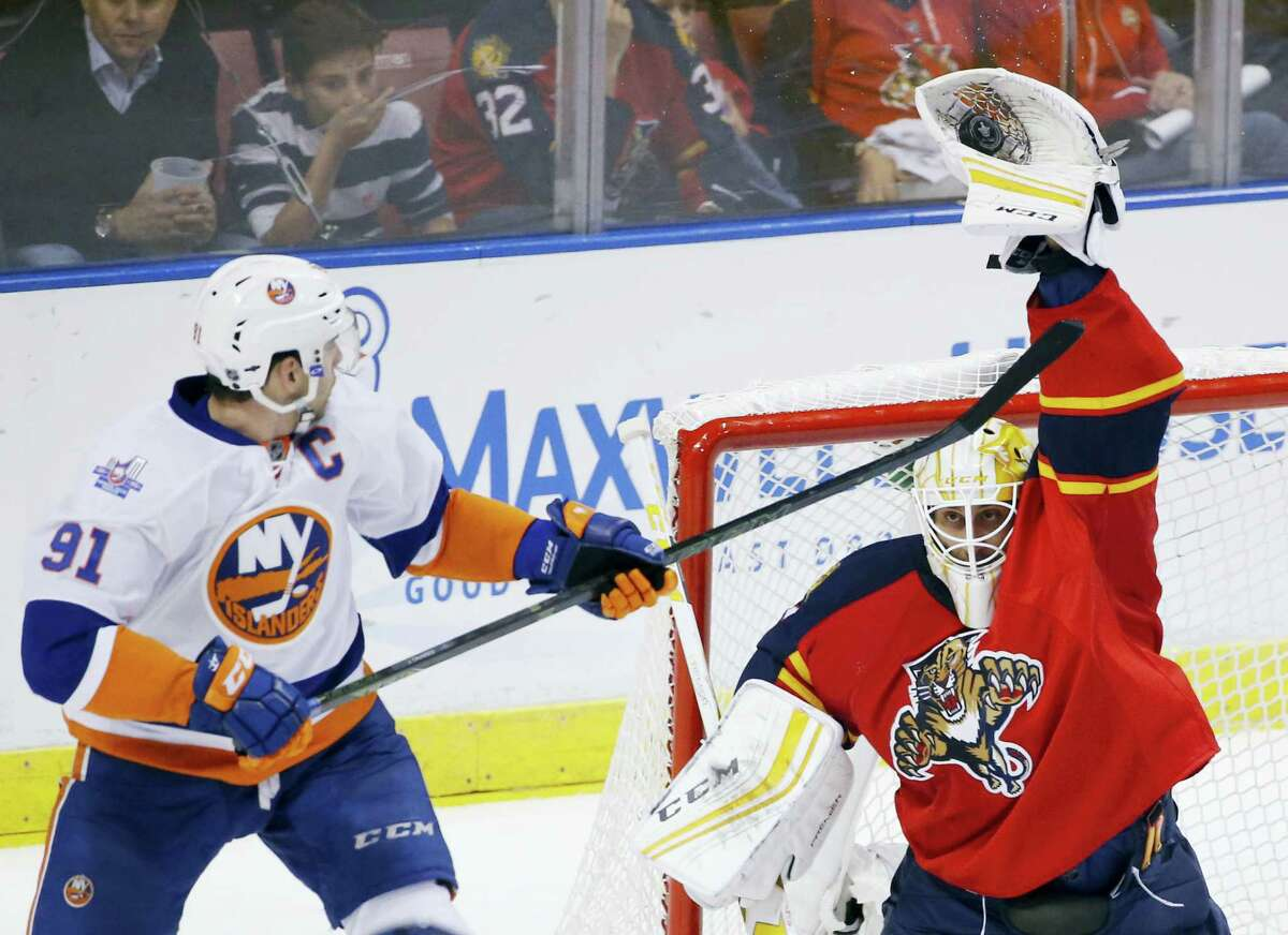 Florida Panthers goalie Roberto Luongo, right, makes a save as Islanders center John Tavares (91) attempts to score during the second period.