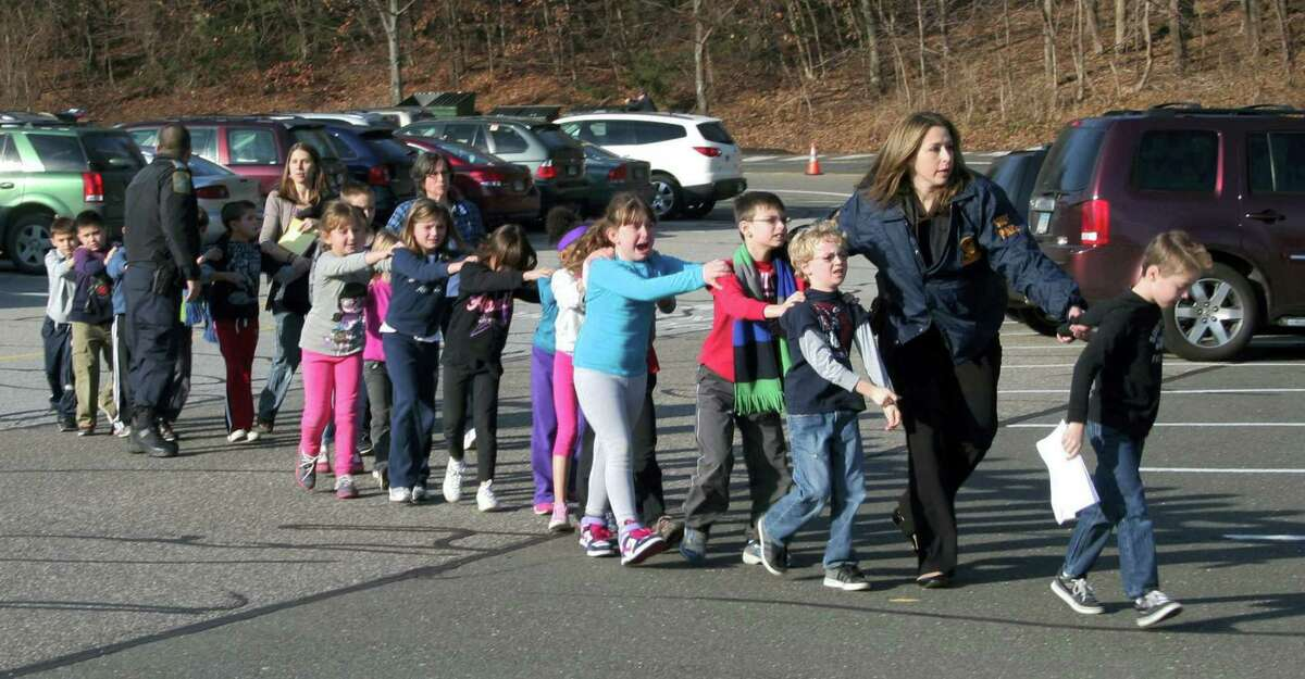 In this photo provided by the Newtown Bee, Connecticut State Police lead a line of children from the Sandy Hook Elementary School in Newtown Friday, Dec. 14, 2012 after a shooting at the school. Recordings of 911 calls from the Newtown school shooting are being released Wednesday Dec. 4, 2013, days after a state prosecutor dropped his fight to continue withholding them, despite an order to provide them to The Associated Press.