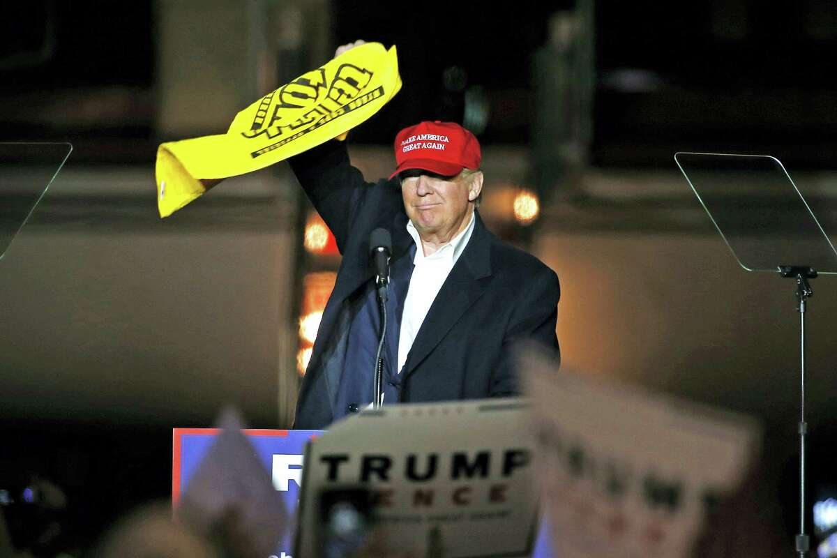 Republican presidential candidate Donald Trump waves a Pittsburgh Steelers Terrible Towel during a plane-side rally in a hanger at Pittsburgh International Airport in Imperial, Pa. on Nov. 6, 2016.
