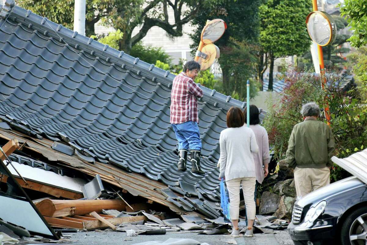 Residents look for an access to their home on the road which is blocked by a collapsed house, in Mashiki, Kumamoto prefecture, southern Japan Saturday, April 16, 2016. A major quake shook southwestern Japan, barely a day after another quake hit the same region.