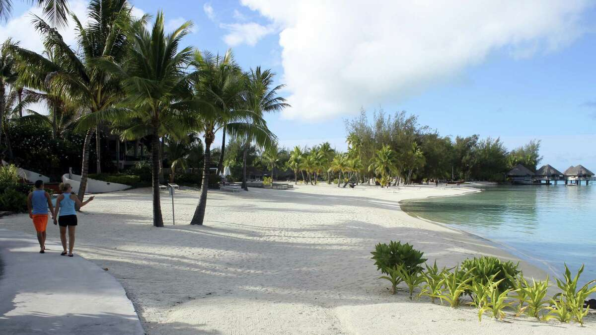 In this Nov. 1, 2016 photo a couple strolls along the sidewalk next to the beach at Le Meridien resort in Bora Bora. Bora Bora offers celebrity-style seclusion and has been a vacation destination for the likes of Justin Bieber, Jennifer Aniston and Usain Bolt. It's located 160 miles from Tahiti with a balmy and relatively consistent temperature of 80 degrees Fahrenheit.