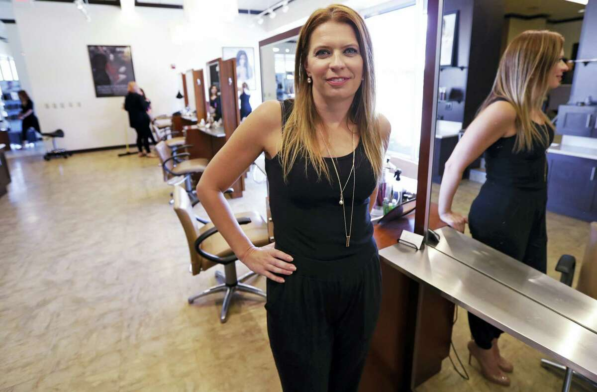 In this Aug. 23, 2016 photo, Christine Perkins, who owns Pyara Spa and Salons at two locations in the Boston area, poses at a stylist station at her salon in Burlington, Mass. Perkins struggles to find candidates to style hair, do manicures and give massages, in part because some beauty schools in the region have closed.